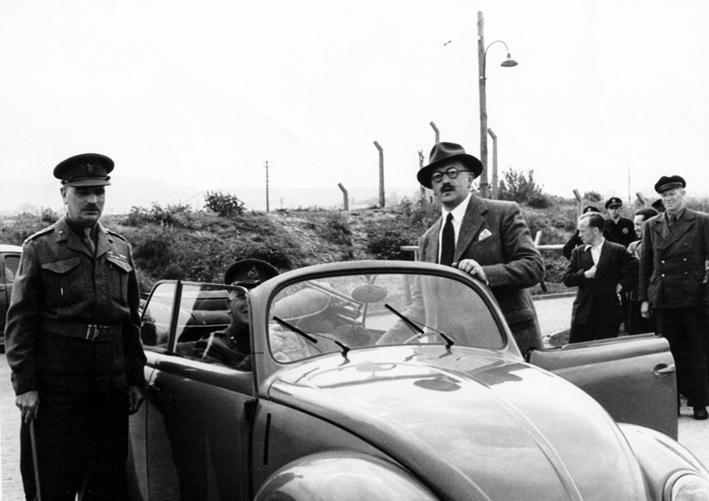 Ivan Hirst (individuo com óculos), alguns oficiais, trabalhadores da VW na retaguarda, e um dos primeiros carochas a ser produzidos após 1945